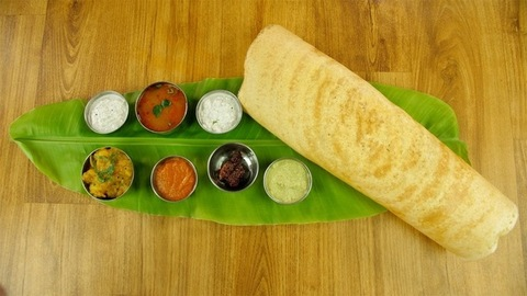 Woman hands serving a bowl of potato masala with South Indian cuisine Dosa