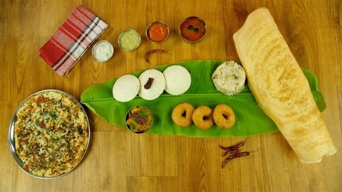 Woman hands serving beautifully plated vegetable Uttapam on a wooden platform