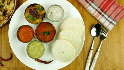 Moving shot of beautifully plated South Indian breakfast on a wooden platform