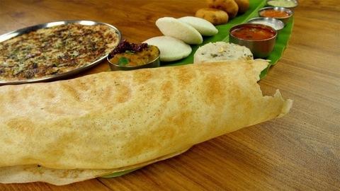 Closeup shot of woman hands eating popular South Indian dosa with sambhar