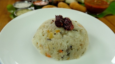 Tilt shot of beautifully plated vegetable Upma garnished with fried red chilies