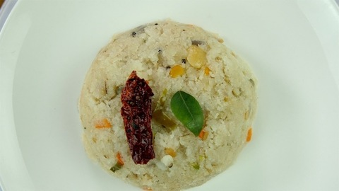 Closeup of popular South Indian breakfast Upma rotating in a ceramic white plate