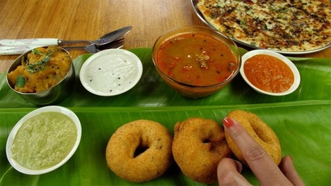 Woman hands serving popular South Indian cuisine Vada on a fresh banana leaf