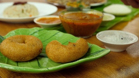 Close up of woman hands eating freshly made Vada with coconut chutney - food concept