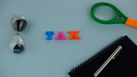 """Closeup shot of a word """"TAX"""" composed of colorful plastic letters on a blue platform"""