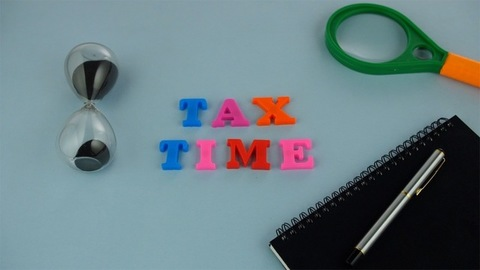 """Racking focus shot of colorful words """"Tax Time"""" against the blue background"""