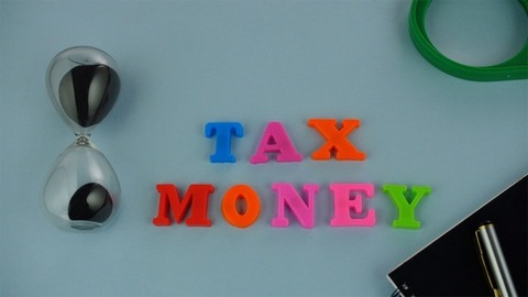 """Tilt shot of colorful words """"Tax Money"""" placed together on the blue background"""