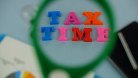 """Woman hands moving magnifying glass left to right over the words """"Tax Time"""""""
