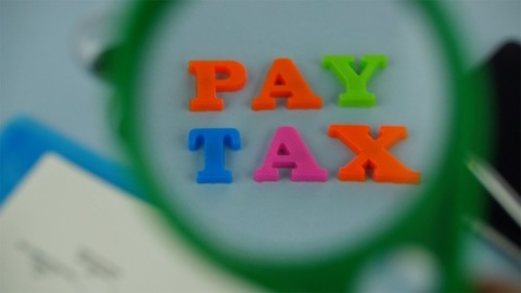 """Closeup shot of woman hands with a magnifying glass over the words """"pay tax"""""""