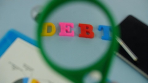 """Closeup shot of woman hands moving a magnifying glass over the word """"Debt"""""""
