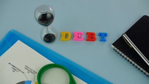"""Pan shot of the word """"Debt"""" written with colorful plastic letters on a blue platform"""