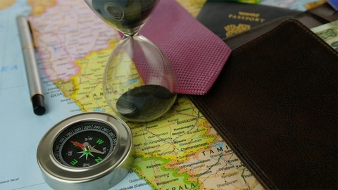 Closeup of a compass showing directions surrounded by travel planning accessories