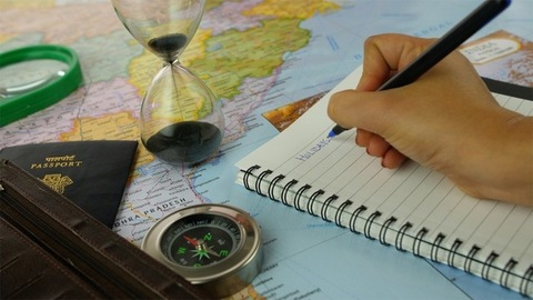Pan shot of Indian female planning for a tour/trip using a map - travel concept
