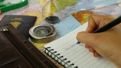 """Closeup shot of woman hands writing the word """"Holidays"""" in her travel notebook"""