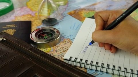 """Closeup shot of woman hands writing a word """"travel"""" in a diary - travel concept"""