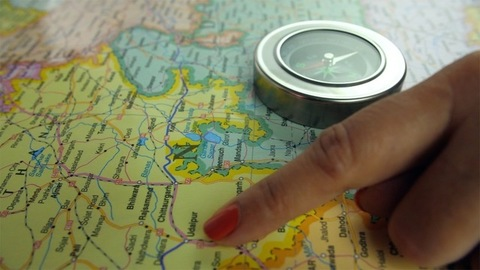 Closeup shot of a woman's hands searching for places to travel in the map of India