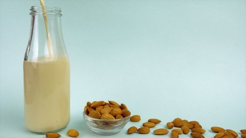 Closeup shot of almond milk is poured into a glass bottle - fitness diet concept