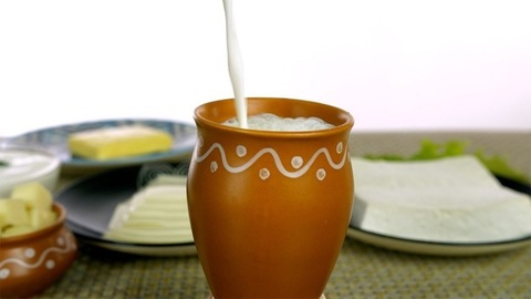 Pouring of milk/Lassi into a designer Kulahad surrounded by various dairy items