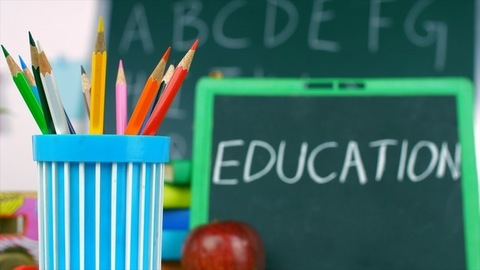 """Closeup of a slate with the word """"Education"""" placed next to colorful pencil colors"""