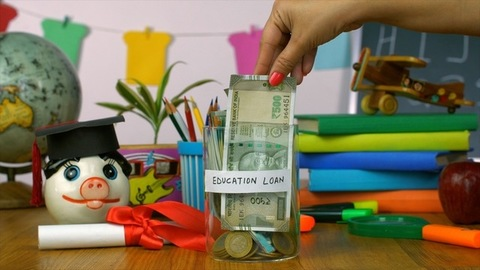 """Closeup of woman hands saving money in a container with """"Education Loan"""" label"""