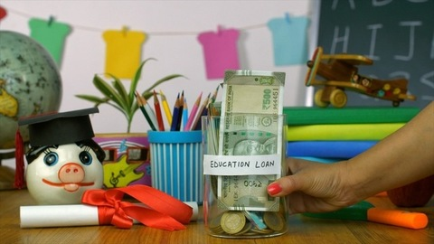 "Woman hands placing a jar with ""Education Loan"" label on a wooden platform"