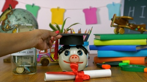 Closeup shot of a woman's hand placing a small graduation cap on a money bank