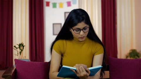 Indian female with poor eyesight wearing spectacles/eyeglass while reading