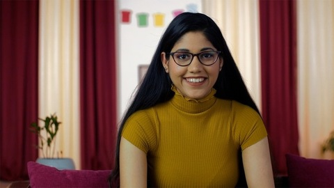 Portrait of a smiling Indian girl holding and wearing a stylish eyeglass
