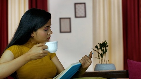 Young Indian woman busy reading a novel while drinking tea/coffee