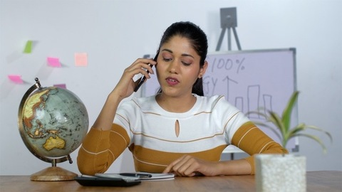 Young working woman talking on her smartphone while working in the office