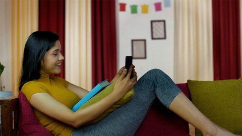 Cheerful young female on her sofa making a video call on her smartphone