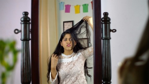 An upset Indian teenager touching her frizzy dry hair looking in the mirror
