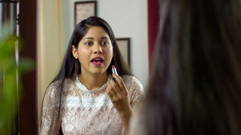 Portrait of a cheerful working girl applying pink lipstick in front of a mirror