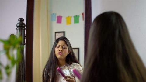 Indian working woman brushing hair in front of a mirror - worried about hair loss
