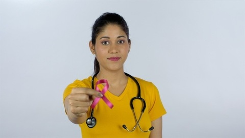 Young doctor with a stethoscope holding pink breast cancer awareness ribbon