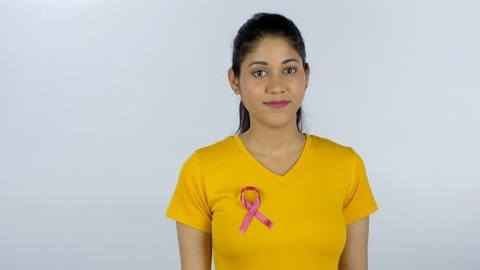 Pretty young lady putting on a pink breast cancer awareness ribbon on her T-shirt