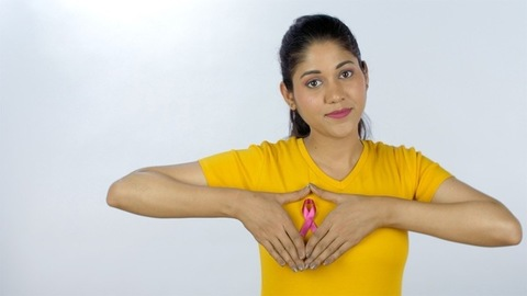Indian girl showing heart symbol near a pink ribbon to support breast cancer awareness