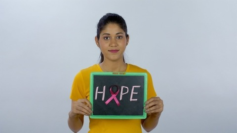 A young girl holding a slate with the word Hope written on it for patients