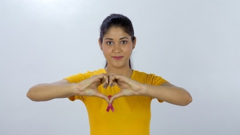 Woman with a pink breast cancer awareness ribbon showing a heart symbol with hands