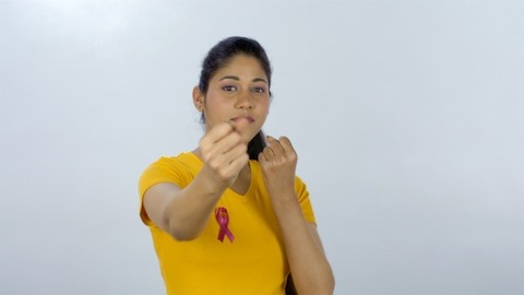 Young woman pointing to pink cancer ribbon on the T-shirt - breast cancer awareness