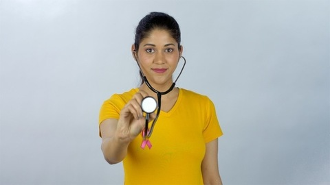 Young aspiring woman doctor with a stethoscope and a pink cancer ribbon