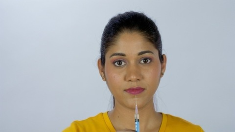 Smart beautiful female with a medical syringe on her lips - cosmetology concept