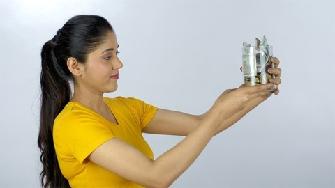 Smart Indian woman happily checking her saved money kept in a glass jar
