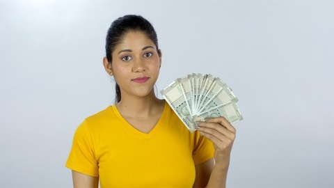 Young Indian girl proudly showing her last month's salary - financial planning