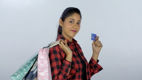 Confident Indian girl happy after doing shopping with her debit/credit card