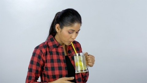 Active Indian girl having a cool refreshing drink/cocktail from a glass