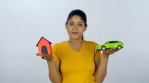 A modern girl with a model of house and car thinking about her future plans