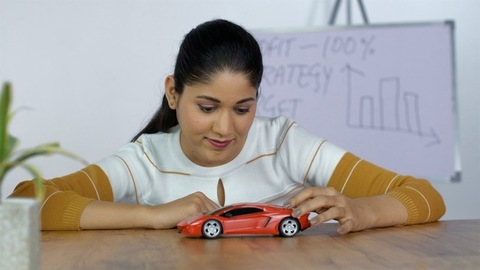 Young Indian office employee with a car model - future aspirations