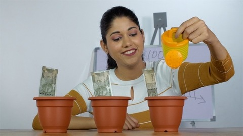 Pretty Indian girl watering the notes in plant pot - Saving money for future, Investment
