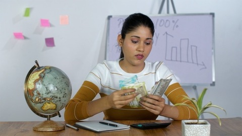 Attractive Indian working woman counting Indian currency notes and tensed